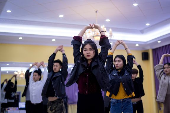 """This picture taken on March 14, 2017 shows Wang Xin (C) attending a dance class at the Yiwu Industrial & Commercial College in Yiwu, east China's Zhejiang Province. Hordes of Chinese millennials are speaking directly to the country's 700 million smartphone users, streaming their lives to lucrative effect, fronting brands and launching businesses. They are known as """"wanghong"""" -- literally hot on the web -- and they now represent a multi-billion-dollar industry, becoming so big that it has its own university curriculum. At Yiwu Industrial & Commercial College, classrooms for the 34 mostly female students are typically dance studios, catwalks strafed by flashing lights, and bustling makeup rooms. / AFP PHOTO / Johannes EISELE / TO GO WITH Lifestyle-celebrity-retail-China-internet, FEATURE by Albee ZHANG (Photo credit should read JOHANNES EISELE/AFP/Getty Images)"""