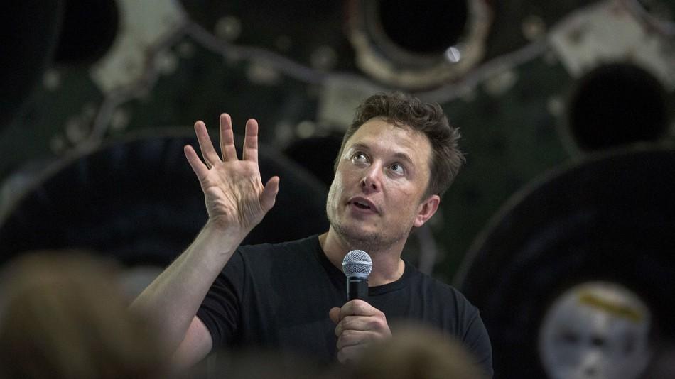 Elon Musk speaks near a Falcon 9 rocket.