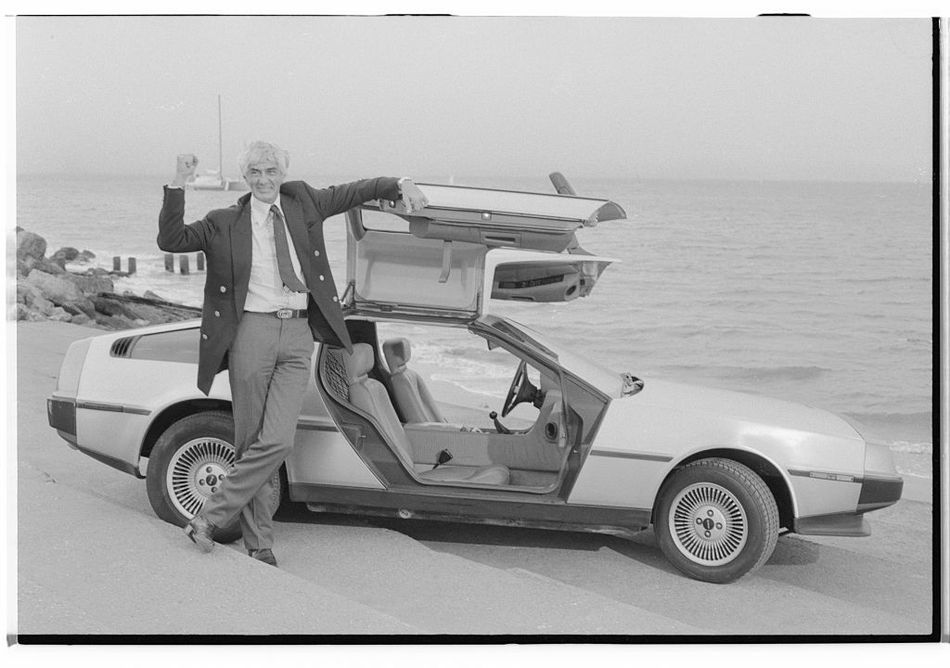 John DeLorean poses with his car.