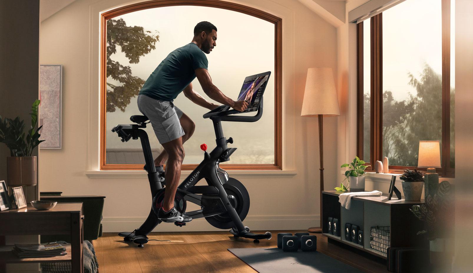 Person riding Peloton bike plus, living room
